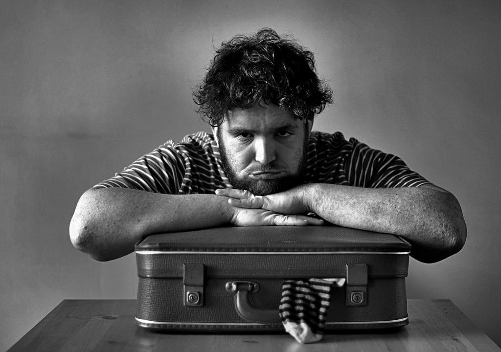 Frusttrierter Mann beim Koffer packen
