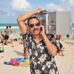 Mann am Strand mit Kofferradio auf der Schulter